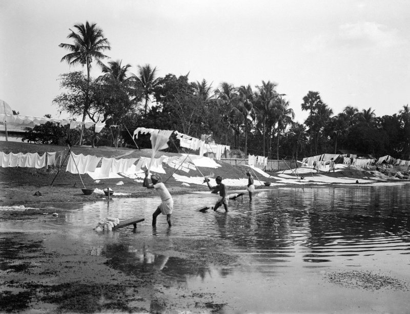 Men washing laundry on a riverbank at a dhobi ghat.  Unknown location.