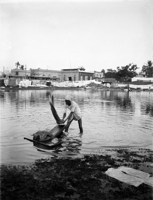 Man washing laundry on riverbank at a dhobi ghat.  Unknown location.
