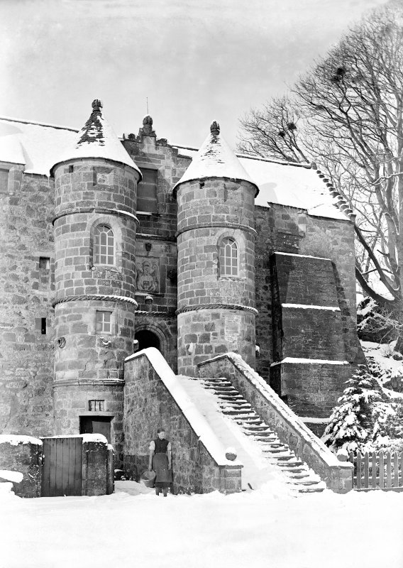 View of entrance to Rowallan Castle, Ayrshire, taken from South and showing a woman standing in the snow.