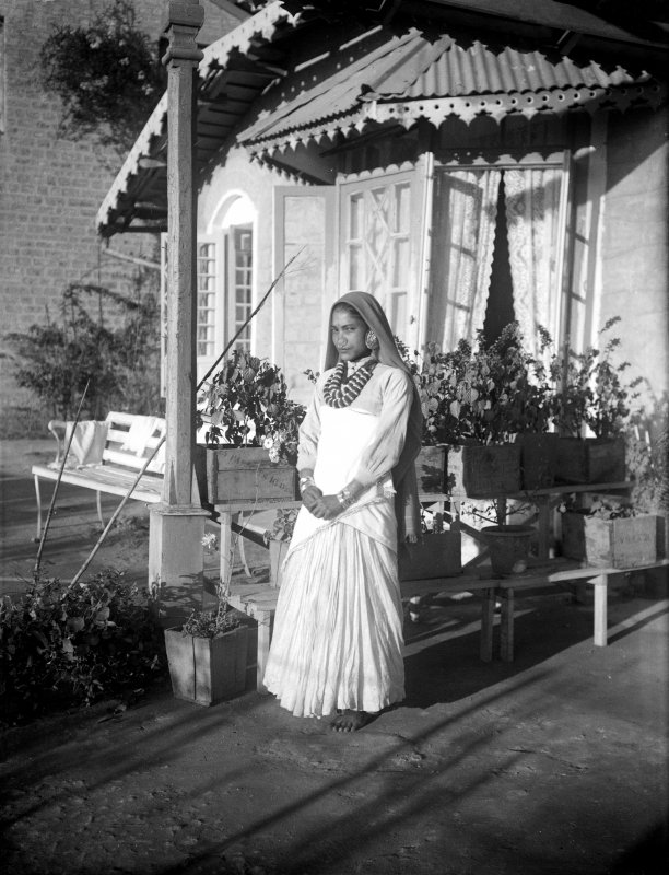 Woman standing outside a house, possibly a member of domestic staff.  Unknown location, possibly in Darjeeling or north Bengal.
