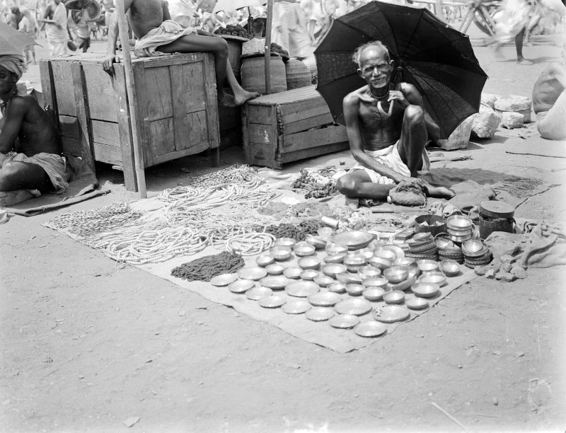 Street vendor selling bowls and necklaces.  Unknown location.