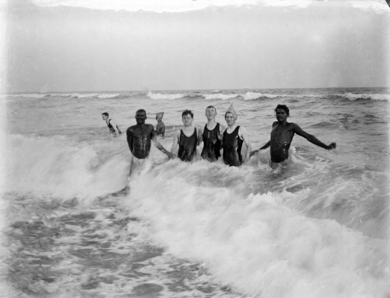 Puri, unknown men swimming in the sea with 'nulias' in trademark woven hats.  Nulias are local men who are on hand to help swimmers in the currents.