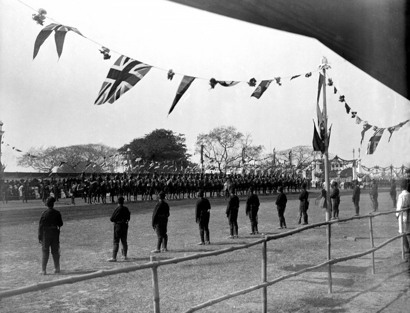 Military group lined up on the riverside, Kolkata, for the arrival or departure of the British royal visit.