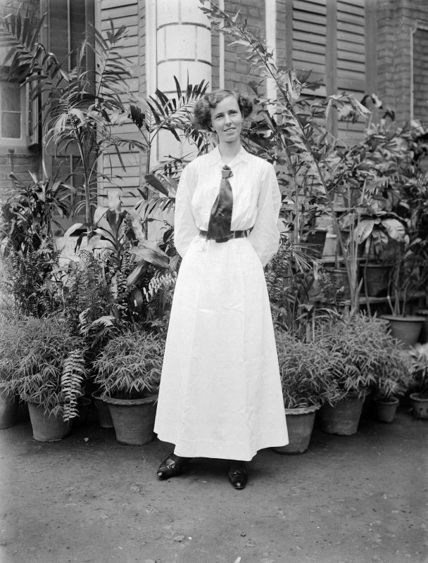 Unknown woman standing outside house. Unknown location.