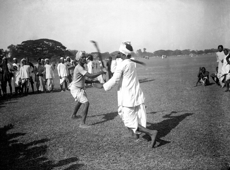 Two men stick dancing with onlooking crowd, Maidan, Kolkata.