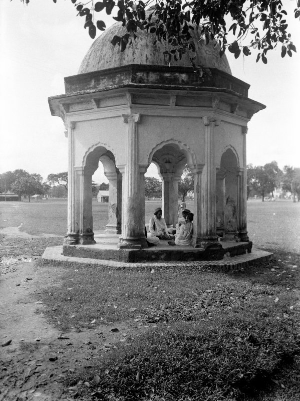Group seated in small pavilion at edge of Manoar (Monohur) Doss's Tank, Maidan, Kolkata.  The pavilion is one of four, one at each of the corners of the tank.