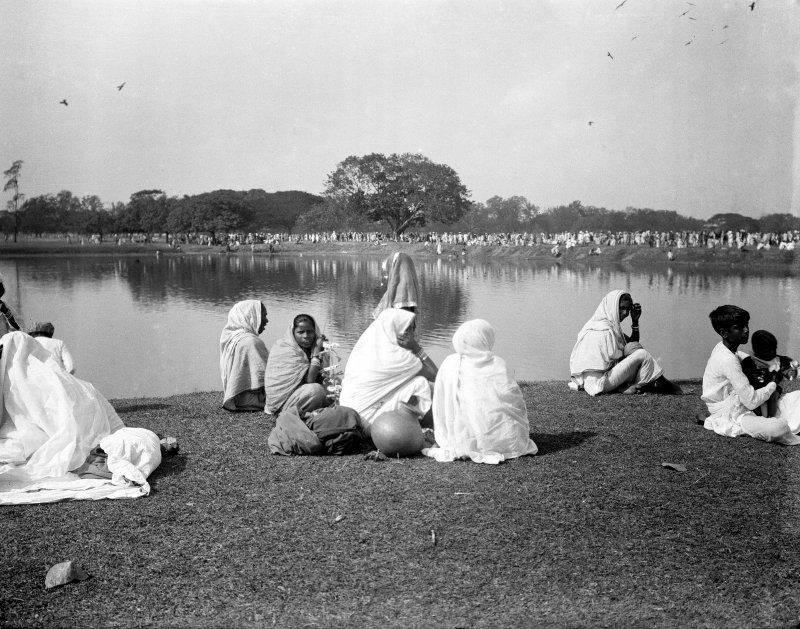Group seated near water tank, probably on the Maidan, Kolkata.  The group are likely to be pilgrims from outside West Bengal.