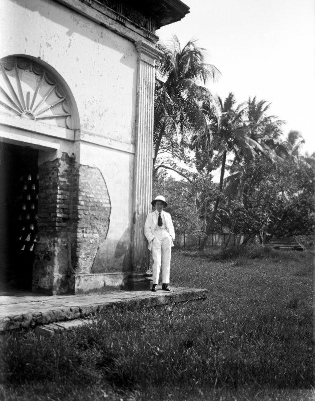 Unknown man standing outside building. Unknown location.