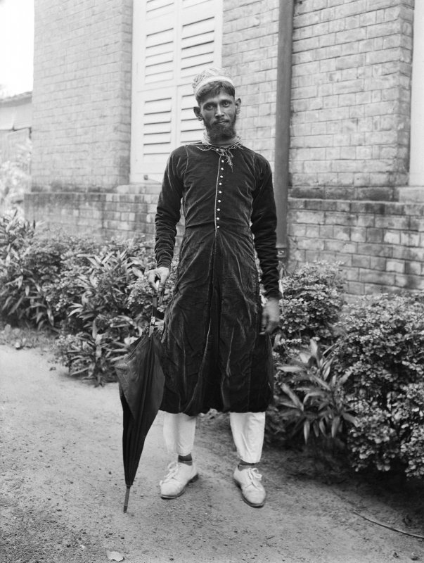 Man, possibly a domestic servant, outside a building. Unknown location.