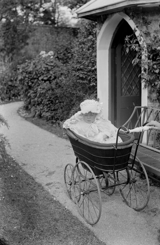 Photograph of David Beveridge (1886-1915), son of Erskine Beveridge, in perambulator outside garden house at Kirkmay House, Crail.