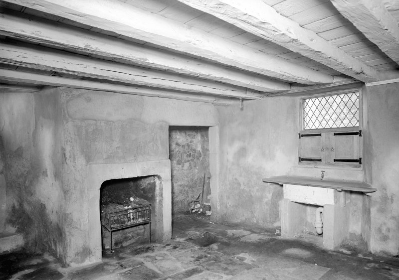 View of Scullery (?), wooden beamed ceiling and fireplace in South wing.