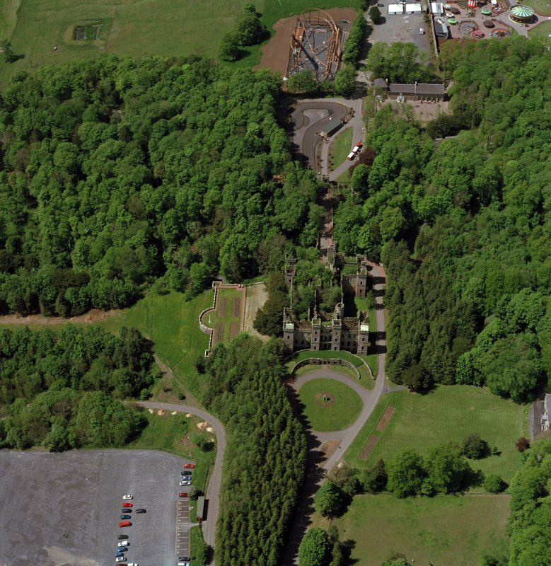 Oblique aerial view of Loudoun Castle, gardens, estate policies and fairground, taken from the W.