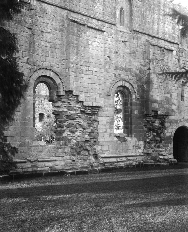View of E wall and buttresses between windows.