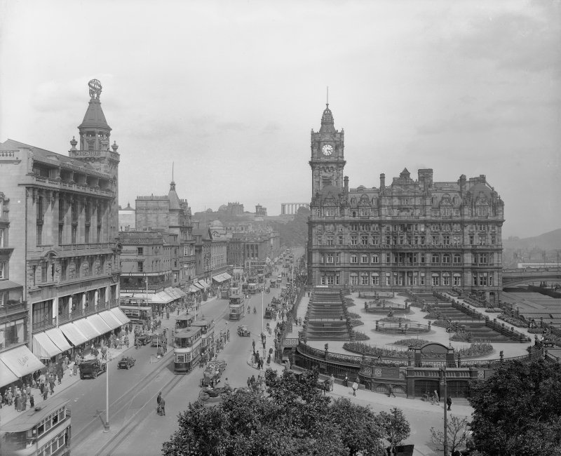 General view of Princes Street looking east towards Calton Hill showing Waverley Gardens, the North British Hotel and a busy street full of shoppers, trams, cars and horse drawn carriages.