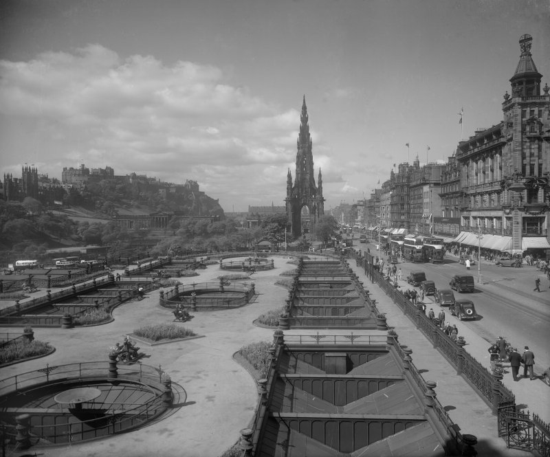 General view of Princes Street looking westwards showing the Castle, Mound, Scott Monument, Waverley Gardens and a busy street with trams, pedestrians and cars