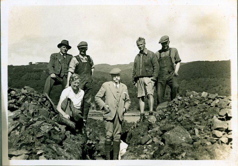 Excavations at Eilean Buidhe dun in August 1936. One of a number of important archive photographs held by Bute Museum, this image shows Dr J N Marshall in the trench flanked by his daughter Dorothy and J Harrison Maxwell, who directed the excavations. The photograph was taken from the SW showing one of the trenches cut through the rampart; the building in the background is the boat house at Caol Ruadh School. © Bute Museum
