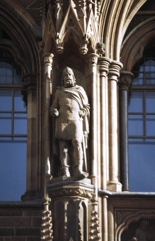 View of statue of Malcolm III, King of Scots, in left upper niche of main entrance, N facade.