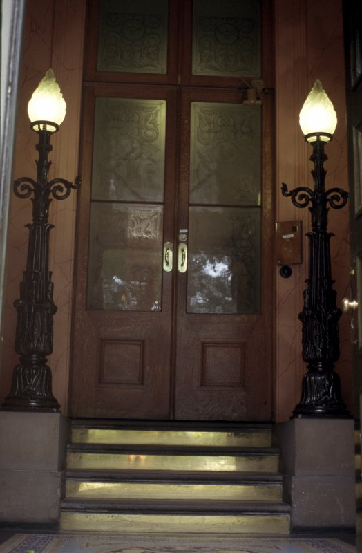 View of cast-iron lamps, one either side of steps leading from foyer to inner door.