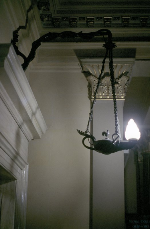 View of hanging lamp, one of a pair hanging from brackets either side of the foot of the stairs.