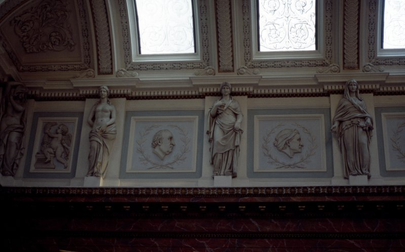 View of the frieze in the Hall, showing portrait profiles of James Gregory and John Hunter, with representations of Hygeia, and a panel carved with a cherub.