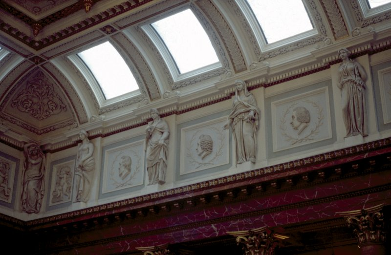 View of the frieze in the Hall, showing portrait profiles of William Harvey, Alexander Monro primus and William Cullen, with representations of Hygeia, and two panels carved with a cherub.
