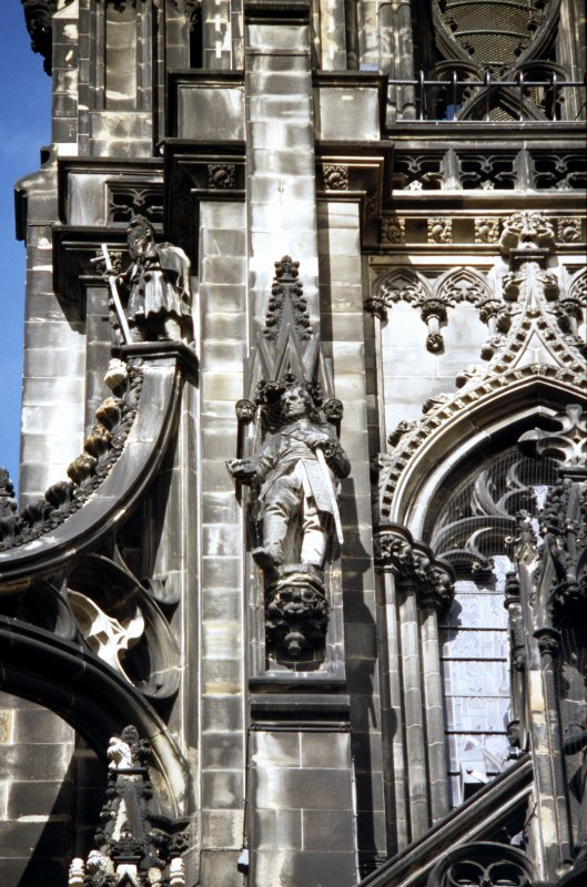 View of statue of Balfour of Burley, on left side of museum window, S side; and statue of a monk at the top of the SW flying buttress.