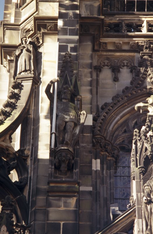 View of statue of Ivanhoe, on left side of museum window, E side; and statue of a nun at the top of the SE flying buttress.