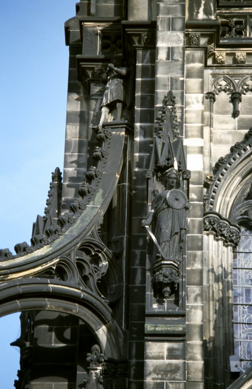 View of statue of Helen Macgregor, on left side of museum window, W side; and statue of a Knight Templar at the top of the NW flying buttress.