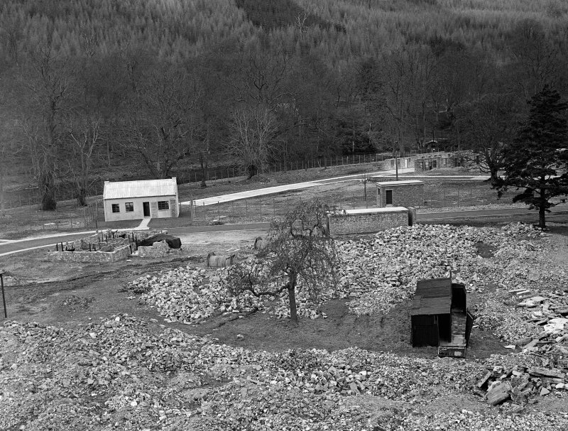 Taymouth Castle, Military Camp. View of training area - looking North from Rescue Tower showing rubble in foreground, gas compound with 'Chlorine' Cottage on left, larch trees of Drummond Hill in background.