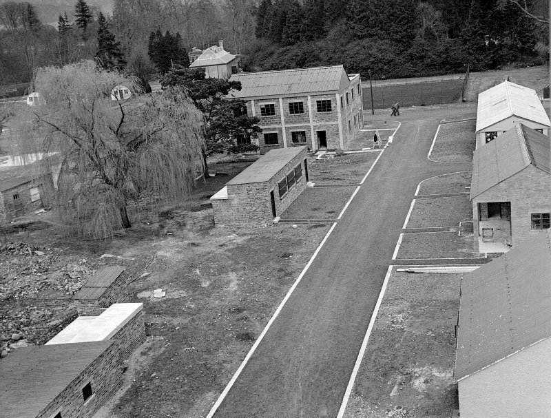 Taymouth Castle, Military Camp. View of training area - looking East from Rescue Tower towards tennis courts, buildings flanking roadway reading left to right, Casulty Handling, Indoor training, Factory building, Knots and lashings, First aid and Casualties and cloakrooms, a cetylene cuttingshop.