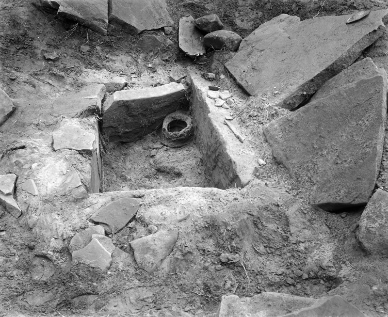 View of Kalemouth cairn during excavation showing cist and food-vessel urn.