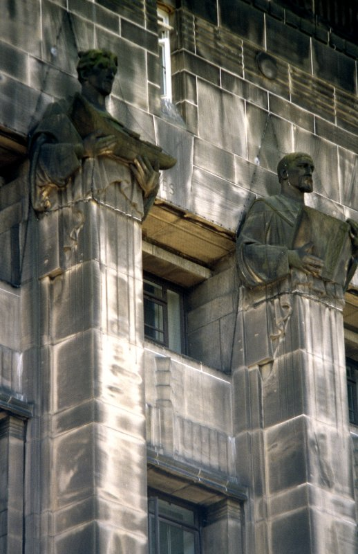 View of sculptures representing Fisheries (left) and Education (right), at top of pillars fifth and sixth from E end of central block.