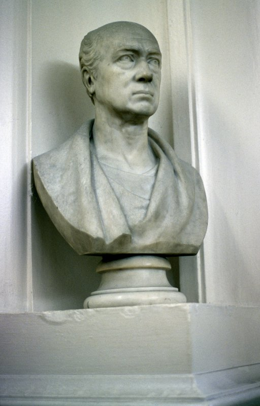 View of bust of an unknown man, in corner niche to left of door at end of box corridor.