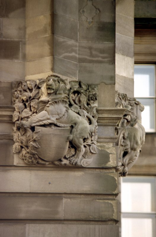 View of carved lion with shield, at NE corner of building, ground floor level (North Bridge).