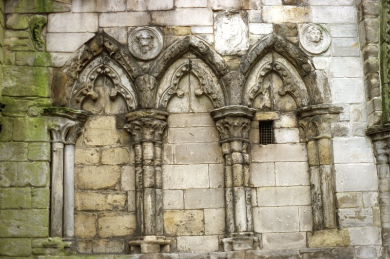 View of two carved medallion heads, between ground floor arches on W facade of Holyrood Abbey.