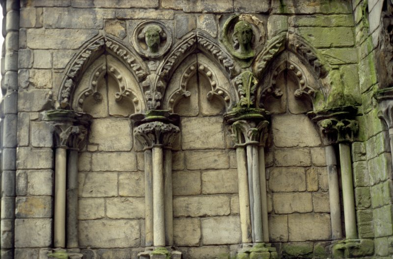 View of two carved medallion heads, between ground floor arches on S side of tower on W facade of Holyrood Abbey.