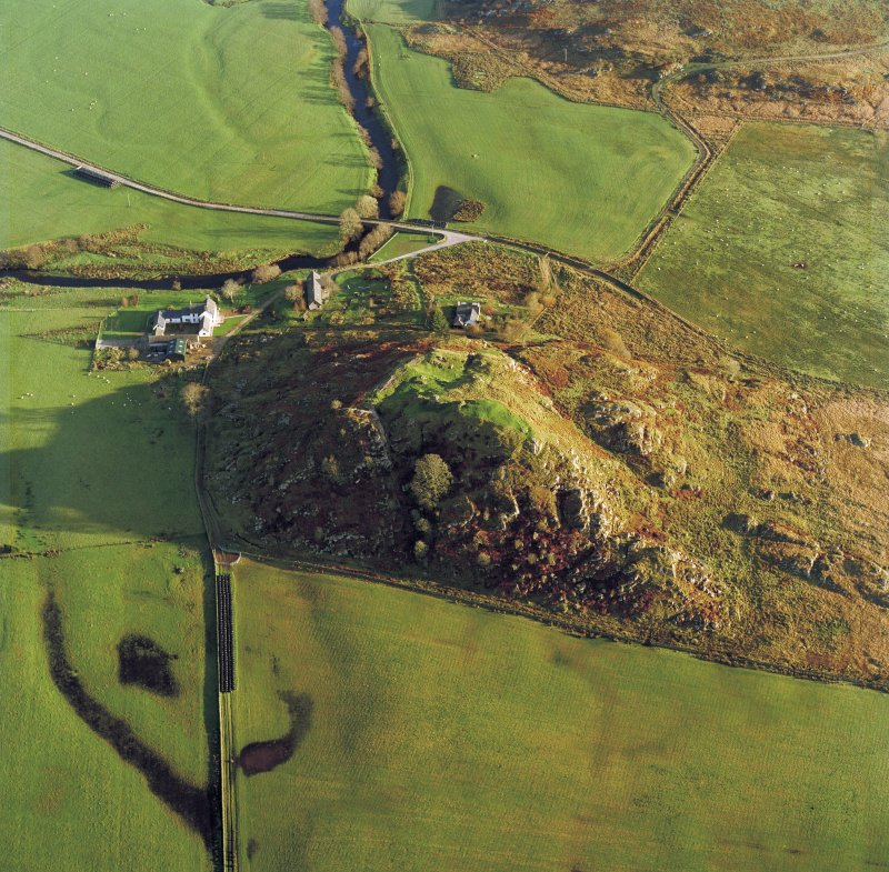 Oblique aerial view centred on the remains of Dunadd fort with the farmstead adjacent, taken from the NW.