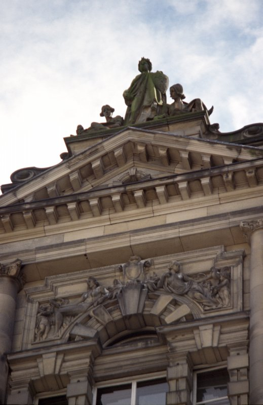 View of N facade of City Chambers (14 Cockburn Street), showing allegorical sculpture group on gable, and spandrel figures below.