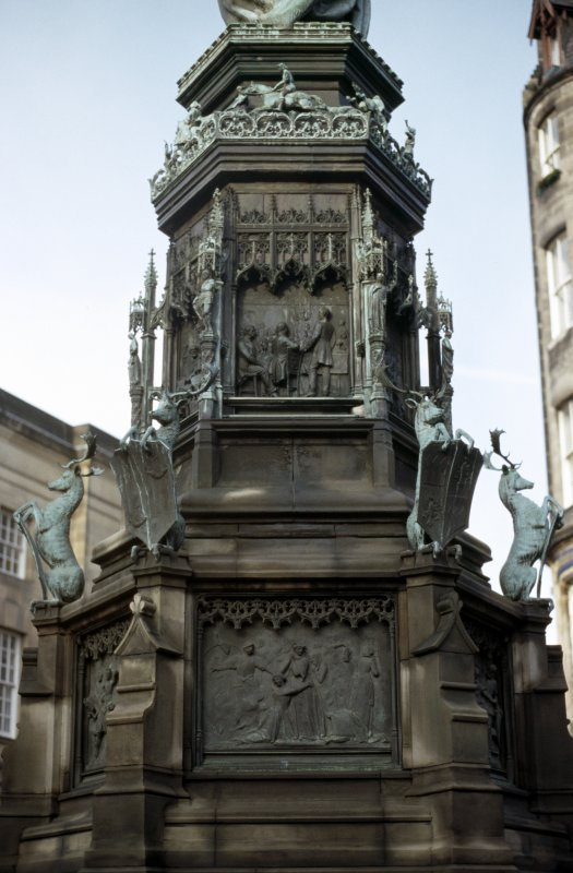 View of SE side of pedestal of Monument to the Duke of Buccleuch, showing bronze panels. The upper panel shows the anniversary dinner given by the tenantry of the Duke in Edinburgh in 1878; the lower panel shows the burning of Branxholm by the English in 1532.