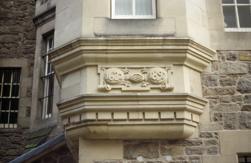 View of carved stone, below second floor window on S wall of Writers' Museum.