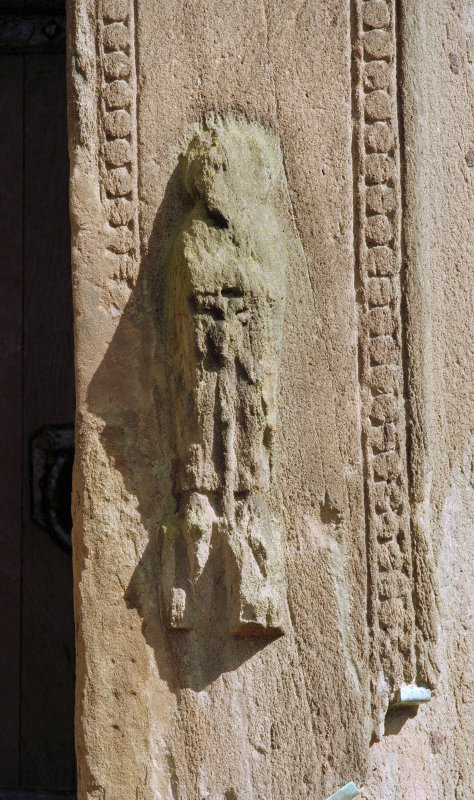 Detail of carved figure to right of doorway on W side of tower.