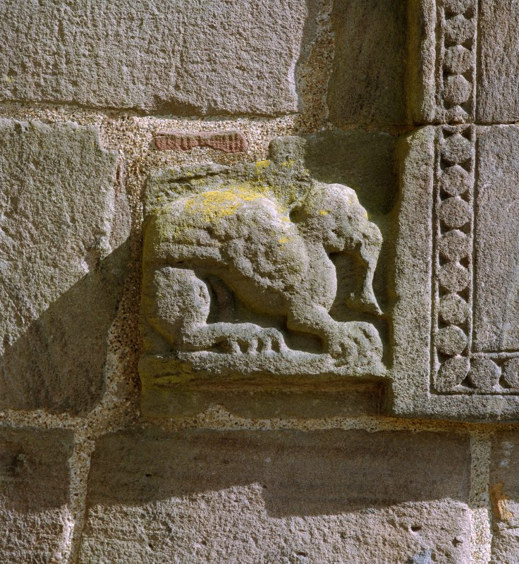 Detail of zoomorphic figure at bottom left hand corner of doorway on W side of tower.
