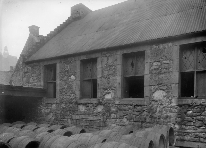 Detail of upper storeys and roof to rear with barrels in foreground