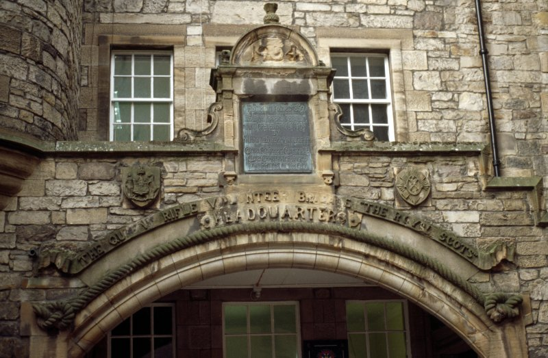 View of archway of former drill hall at 5 Forrest Hill, Edinburgh, showing shields carved with the arms of Edinburgh (left) and The Royal Scots (right), and bronze inscription panel.