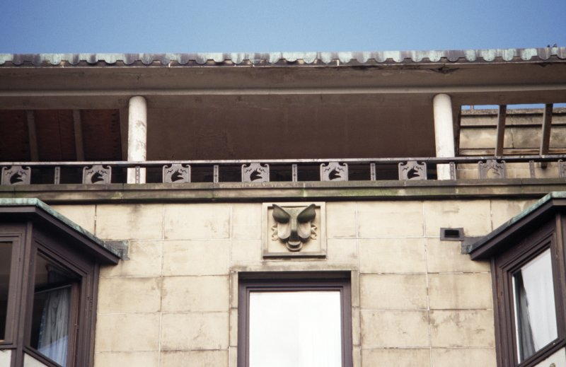 View of stylised mask (one of five), above top floor windows of Mount Royal Hotel, 54-58 Princes Street.