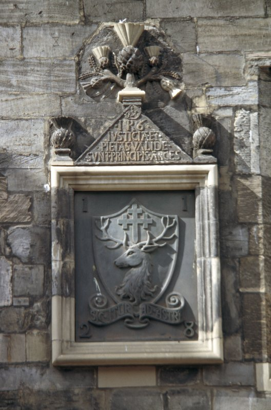 View of carved frame containing shield, with inscription panel and thistles above, between first floor windows of 165 Canongate.