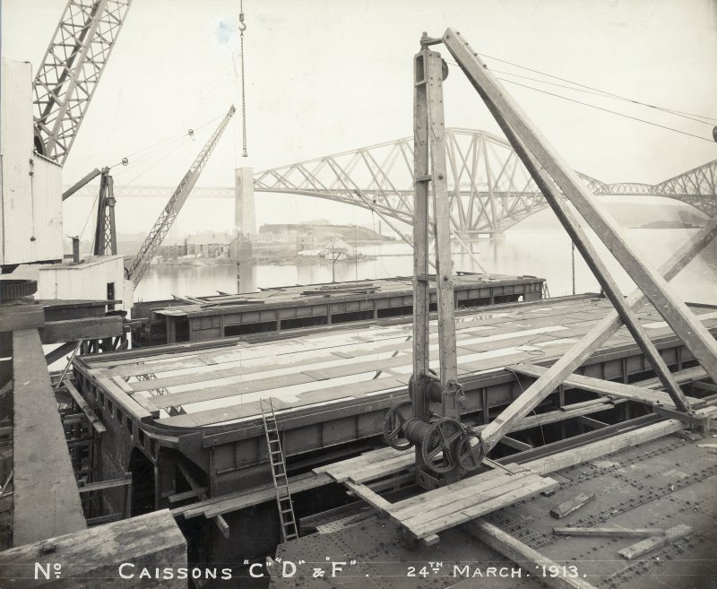 View of caissons, Rosyth dockyard with the Forth Bridge visible in the background. Titled: 'No. Caissons C, D & F. 24 March 1913'.