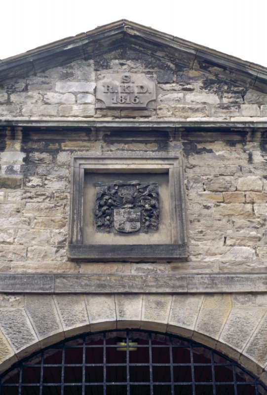 View of coat of arms of the Dick family, in gable above main entrance to stable block.