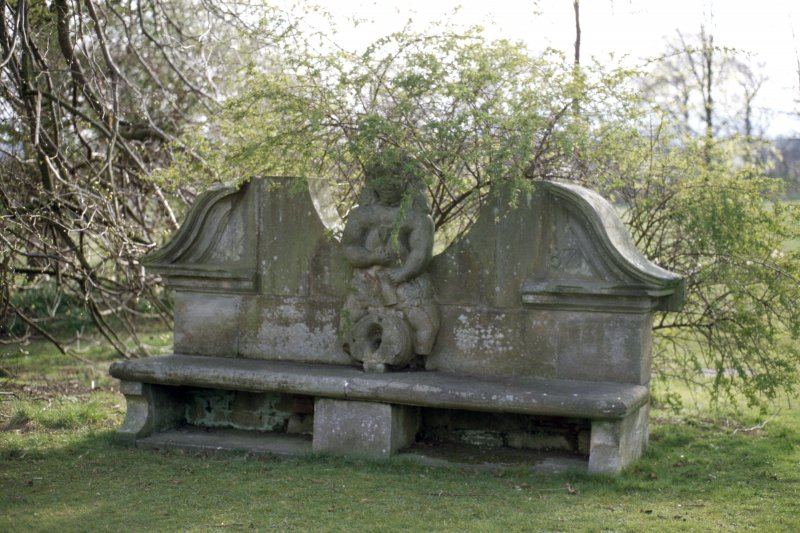 View of bench with statue of Bacchus, in garden to right of main house.