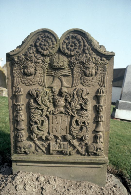 General view of gravestone of Margaret Hill, 1754. Rosettes, crown over crossed palm fronds and vine, double winged souls and pair of double torches. Foliate crest Insc: 'R.H K.M'. Emblems of mortality linked by ribband. (skulls, arrows of Death, hourglass and crossed bones).